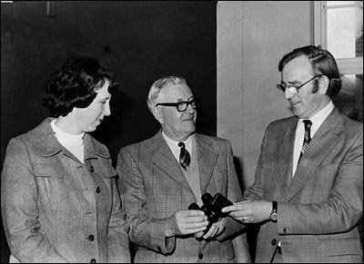 Photograph of Bob Whitworth being presented with binoculars