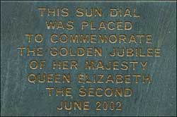 The plaque on the flower bed wall
