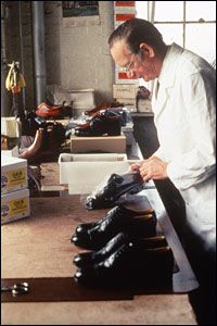 Photogragh of Tom Thacker inspecting shoes